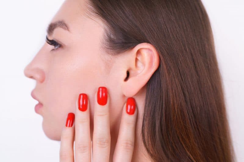 close up of woman pointing to ear