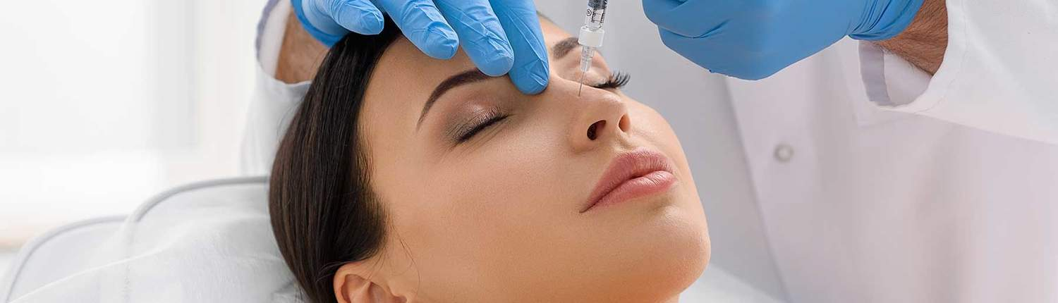 cosmetic surgeon putting needle on womans face